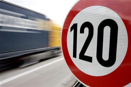 A truck passes a 120 km/h (75 mph) speed limit sign